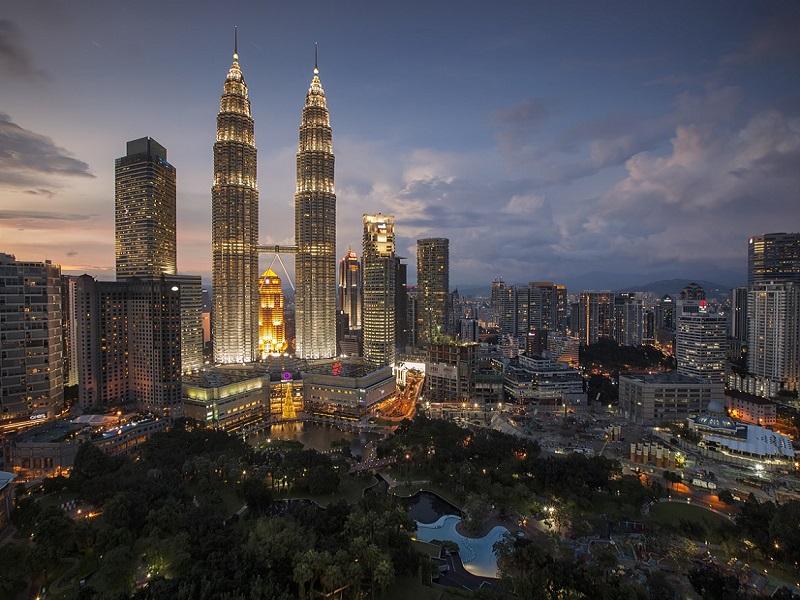 Malaysian capital city Kuala Lumpur in the dark with Petronas Towers in the center.
